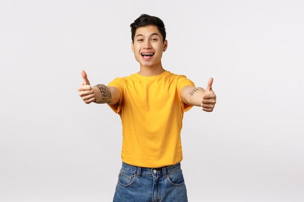 De leuke aziatische mens in het gele t-shirt geven beduimelt omhoog