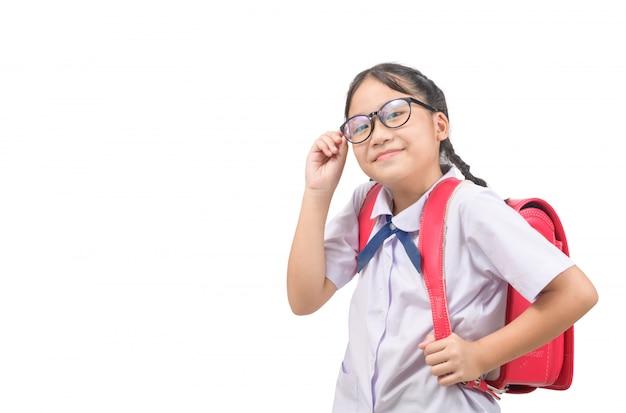 De leuke aziatische studente draagt eenvormig en draagt geïsoleerde schooltas