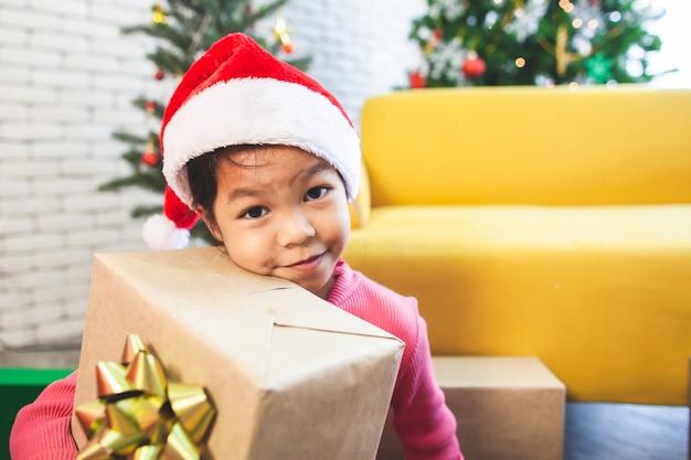 De leuke aziatische verrassing van het kindmeisje met gift en het houden van mooie gift bij kerstmisviering in hand