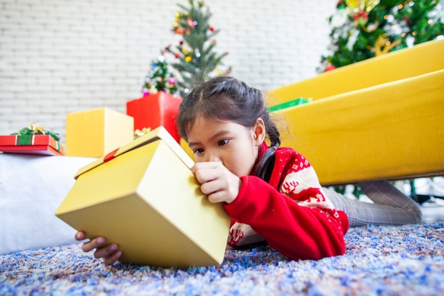 De leuke aziatische verrassing van het kindmeisje met gift en het houden van mooie giftdoos op kerstmisviering in hand