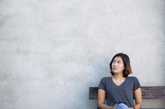 De leuke aziatische vrouw denkt iets op grijze achtergrond