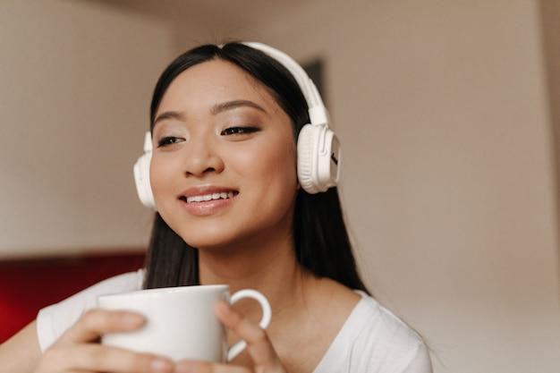 De leuke aziatische vrouw in grote hoofdtelefoons glimlacht en houdt kop thee