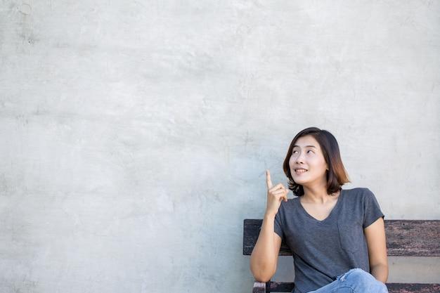 De leuke aziatische vrouw toont iets aan u op de grijze achtergrond.