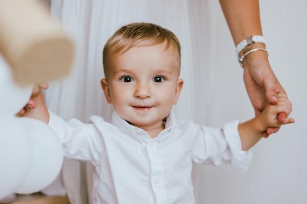 De leuke babyjongen in wit overhemd met handen van zijn moeder in helder binnenlands, sluit omhoog portret