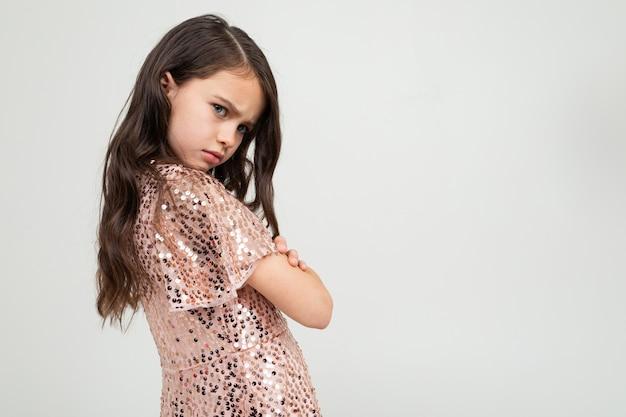 De leuke beledigde meisjes glanzende feestkleding kruiste haar wapens op een witte studiomuur met lege ruimte