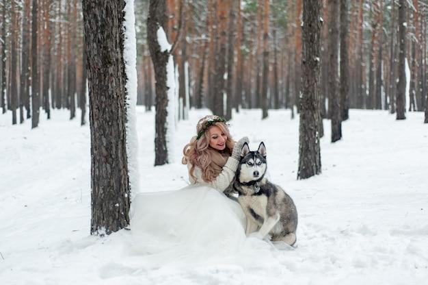 De leuke bruid met kroon speelt met siberische schor op achtergrond van witte sneeuw. winter bruiloft.