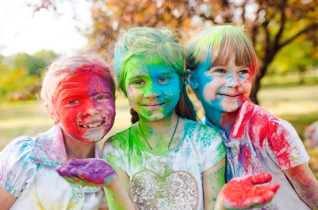 De leuke europese kindmeisjes vieren indisch holifestival met kleurrijk verfpoeder op gezichten en lichaam