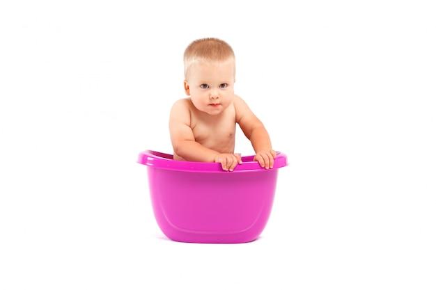 De leuke gelukkige babyjongen neemt bad in ton