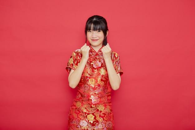 De leuke jonge aziatische cheongsam van de vrouwenkleding met actie voor chinees nieuwjaarconcept