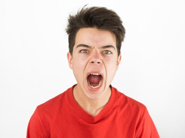 De leuke jonge jongen in rode t-shirt die boos zijn is