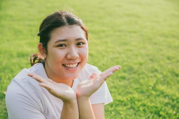 De leuke jonge onschuldige aziatische tienerglimlach stelt haar gezicht voor