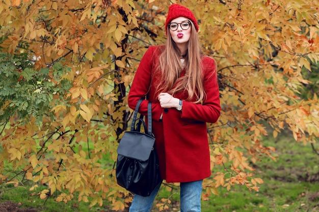 De leuke jonge vrouw verzendt kus. aantrekkelijke dame die rode de herfstkleren draagt