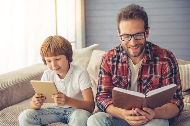 De leuke jongen gebruikt thuis een digitale tablet.