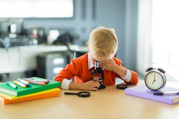 De leuke jongen zit bij het bureau in het bureau, houdt microscoop