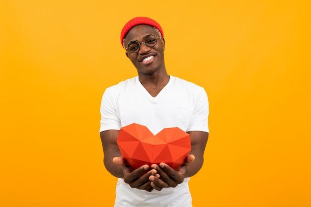 De leuke knappe afrikaanse mens in een wit t-shirt houdt een rood 3d hart stand dat van document voor valentijnskaartendag op een gele achtergrond wordt gemaakt
