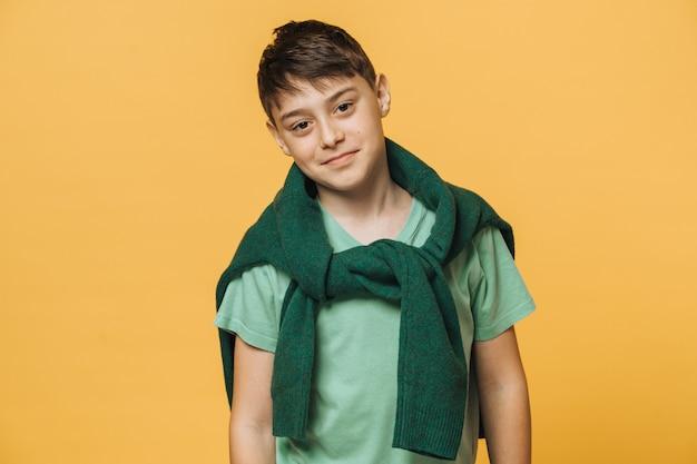 De leuke knappe jongen kleedde zich toevallig over geïsoleerde gele muur slim kijkend. stijlvol tienerconcept.
