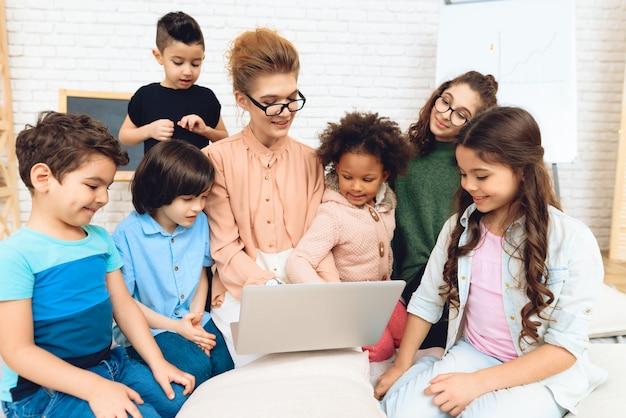 De leuke leraar zit met kinderen die laptop bekijken.