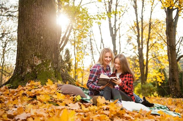 De leuke lezing van het tienermeisje met haar moeder samen in park