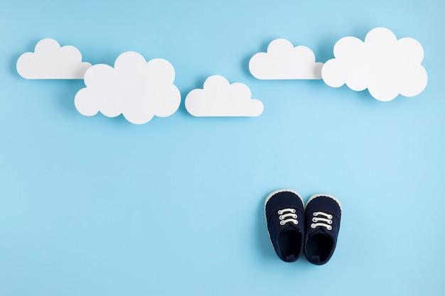 De leuke pasgeboren schoenen van de babyjongen met feestelijke decoratie over blauwe muur.