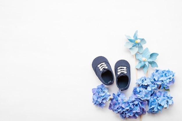 De leuke pasgeboren schoenen van de babyjongen met feestelijke decoratie.