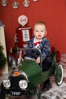 De leuke peuter speelt met speelgoedauto's, berijdt een stuk speelgoed schrijfmachinevliegtuig, gelukkige kinderjaren
