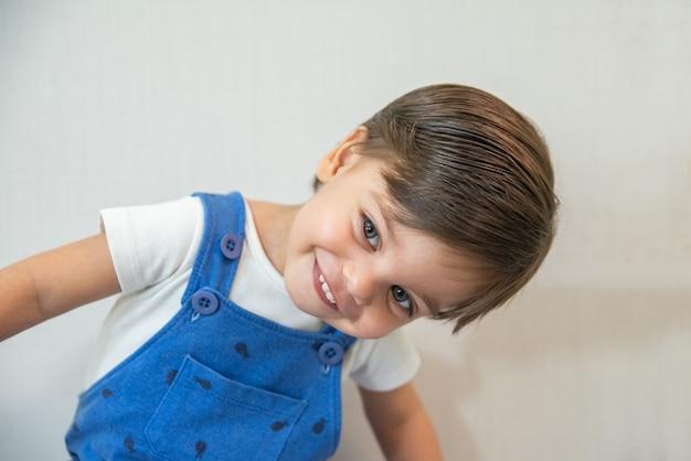 De leuke peuter van de babyjongen - met blauwe kruippakje op witte achtergrond die - glimlacht