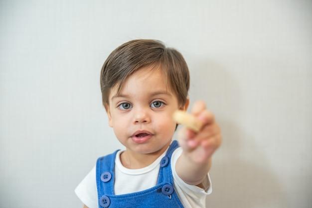 De leuke peuter van de babyjongen - met blauwe kruippakje op witte achtergrond die - wafeltje eten