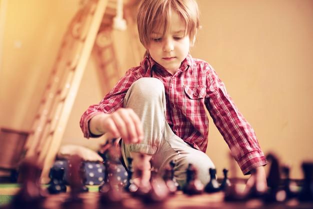 De leuke peuterjongen speelt thuis schaak