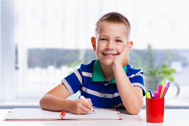 De leuke schooljongen schrijft geïsoleerd op een witte achtergrond