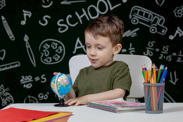 De leuke slimme jongen zit bij een bureau met bol in hand op achtergrond met bord. klaar voor school. terug naar school