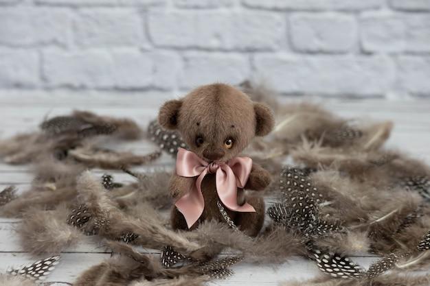 De leuke teddybeer met een roze boog zit op de veren van de kwartelvogel.