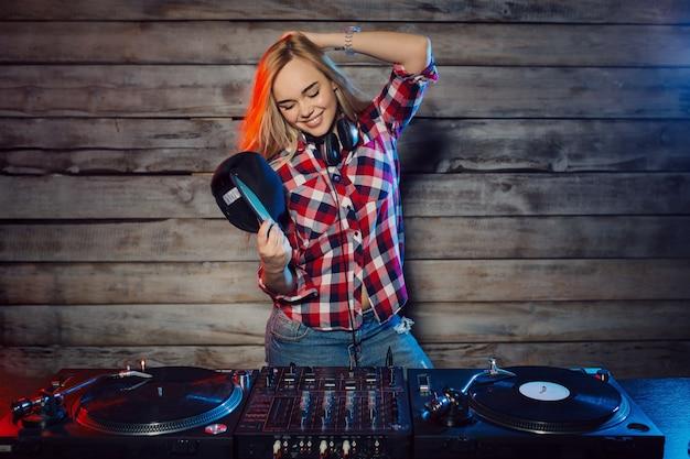 De leuke vrouw die van dj pret speelmuziek hebben bij clubpartij