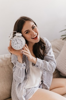 De leuke vrouw in mooie pyjama glimlacht, bekijkt voorzijde en houdt wekker vast
