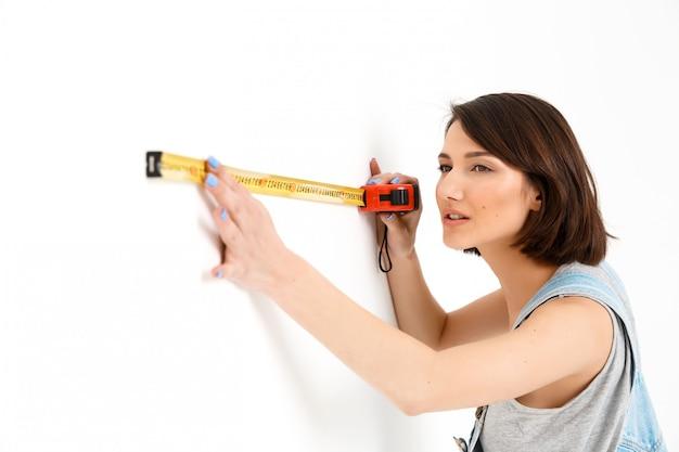 De leuke vrouw met meetlint vernieuwt huis