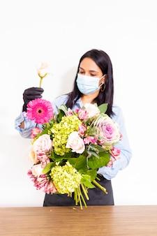 De leuke vrouwenbloemist maakt een boeket van rozen, hortensia's en alstroemerias