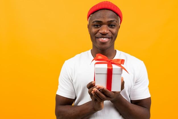 De leuke zwarte amerikaanse mens in witte t-shirt houdt giftdoos op gele achtergrond