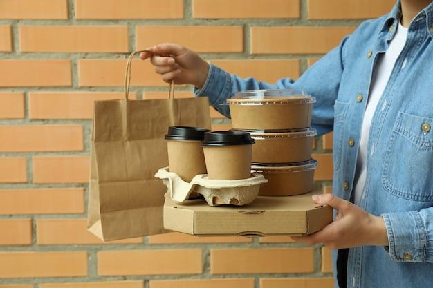 De leveringscontainers van de vrouwengreep voor afhaalmaaltijden op bakstenen muur