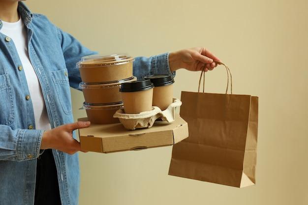 De leveringscontainers van de vrouwengreep voor afhaalmaaltijden op beige ondergrond