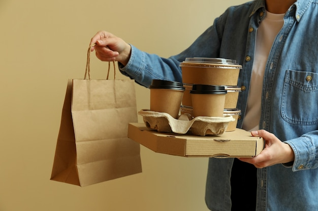 De leveringscontainers van de vrouwengreep voor afhaalmaaltijden op beige