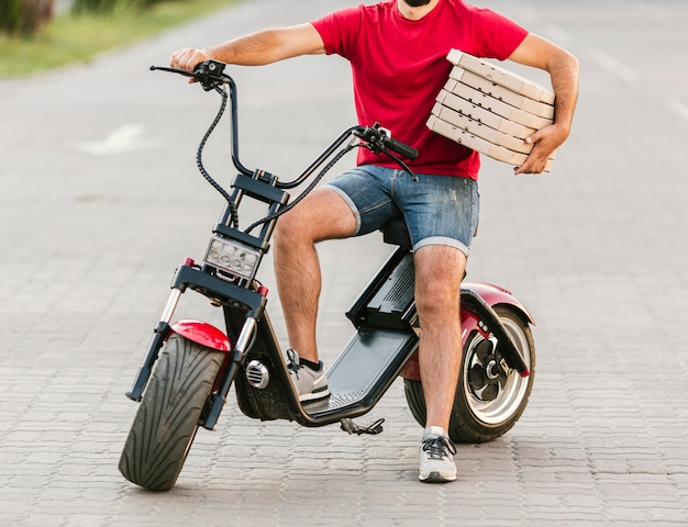 De leveringskerel van de close-up op motorfiets met pizza