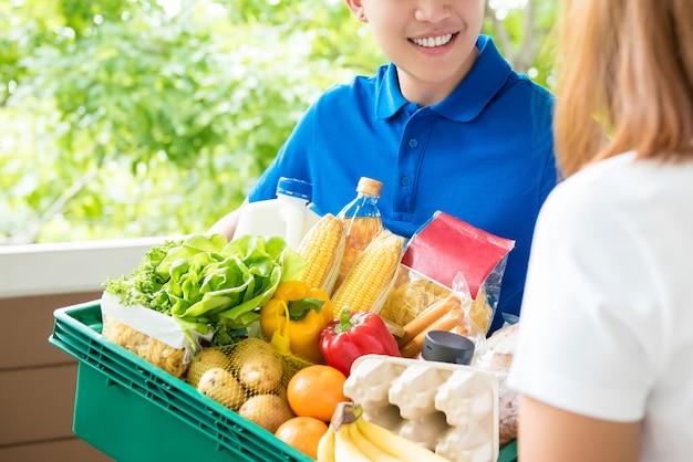 De leveringsman die van de kruidenierswinkel voedsel thuis leveren aan een vrouw