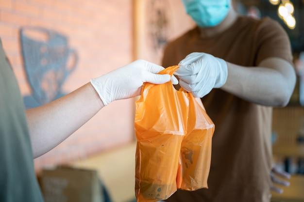 De leveringsman draagt gezichtsmasker en handschoenen die voedselzak voor veiligheidsdienst houden