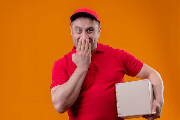 De leveringsmens die rood eenvormig en glb-het pakket van de holdingsdoos dragen die verrast het behandelen van mond kijken met overhandigt geïsoleerde oranje muur