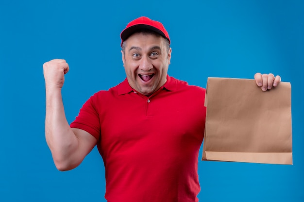 De leveringsmens die rood eenvormig en glb-holdingsdocument pakket dragen ging weg en gelukkige het opheffen vuist na een overwinning over geïsoleerde blauwe muur