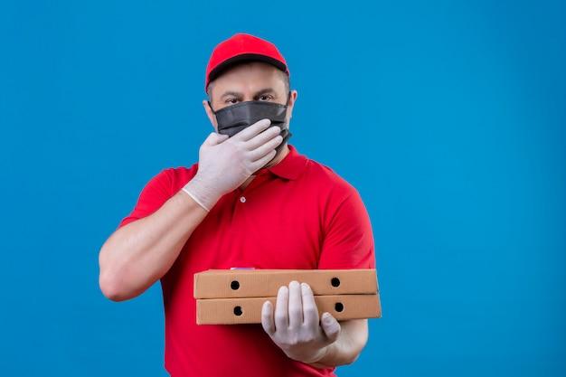 De leveringsmens die rood uniform en glb in de gezichts beschermende pizzadozen dragen die van de maskerholding verraste mond kijken overhandigt blauwe muur