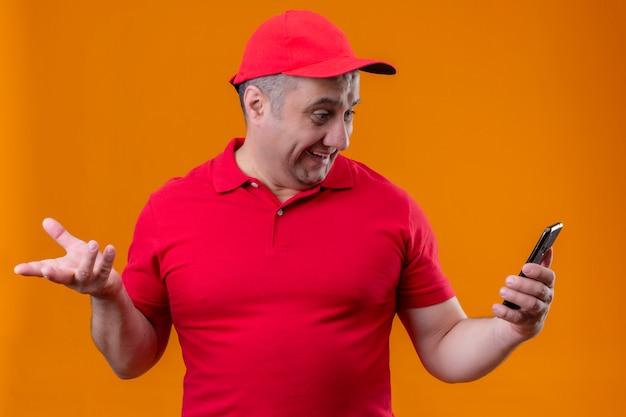 De leveringsmens die rood uniform en glb met mobiele telefoon dragen die verrast met opgeheven kijken overhandigt oranje muur