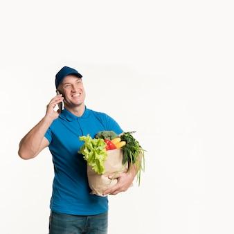 De leveringsmens die van smiley op telefoon spreekt terwijl het dragen van kruidenierswinkelzak