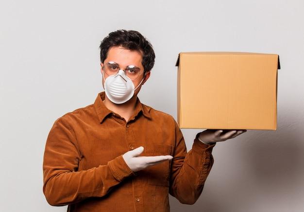 De leveringsmens in masker houdt een pakket