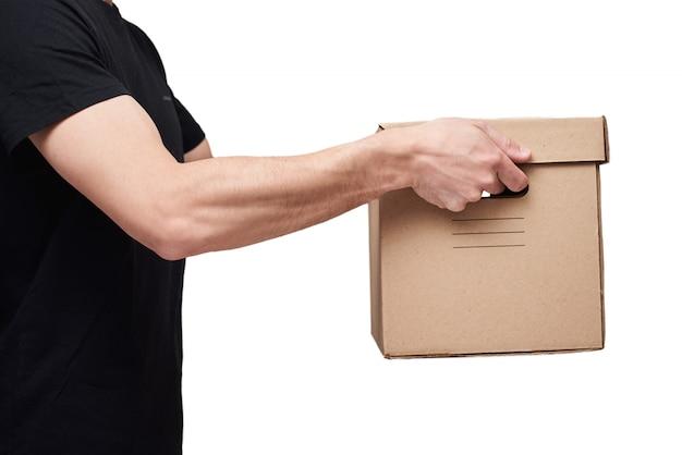 De leveringsmens in zwarte t-shirt houdt kartondoos op geïsoleerd wit. levering dienstverleningsconcept