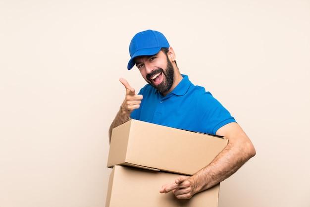 De leveringsmens met baard over geïsoleerde muur richt vinger op u terwijl het glimlachen